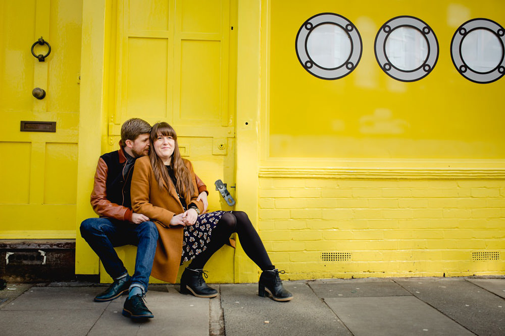 portrait of engaged couple sat outside of yellow building in columbia street market