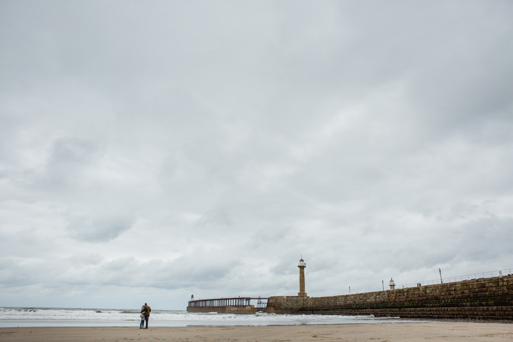 photo of the pier in whitby featuring newly engaged couple