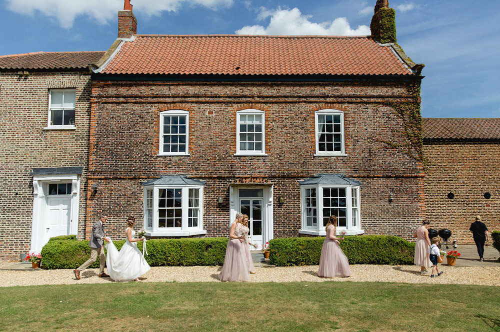 Bride and bridesmaid walking past the front of hornington manor