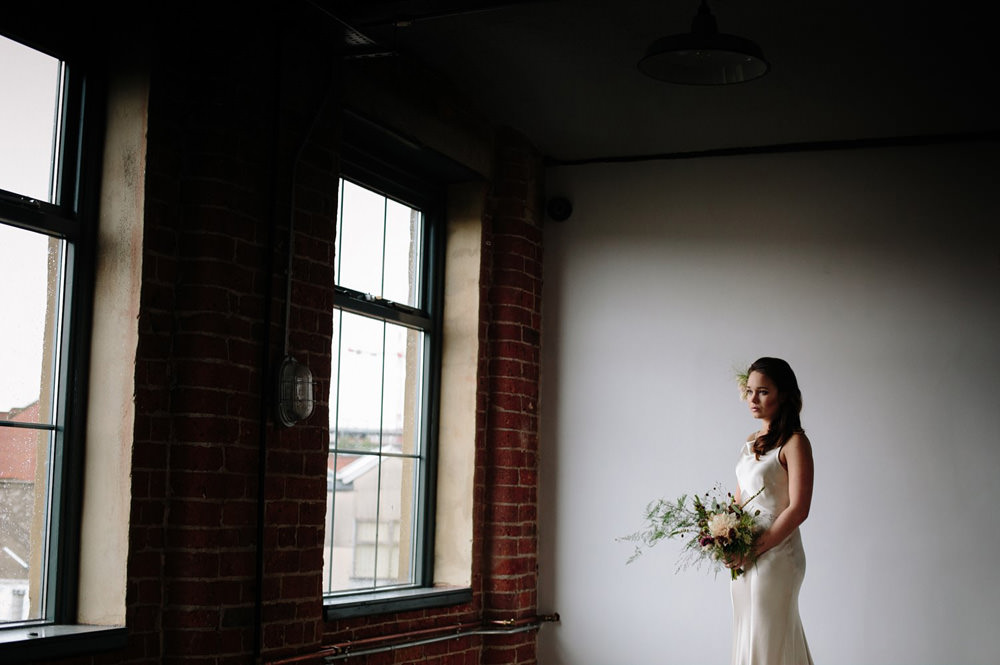 portrait of bride next to windows in mill at northern monk refectory wedding