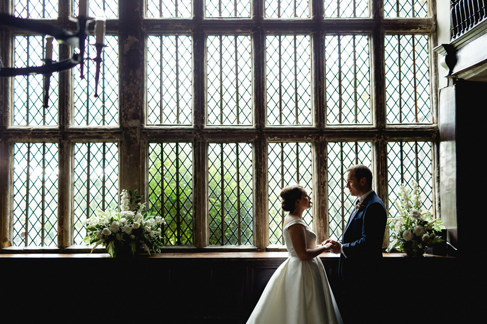 Portrait of wedding couple in front of Oakwell Hall Windows