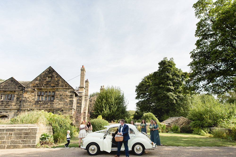 documentary photograph of bride arriving in vintage morris minor at oakwell hall