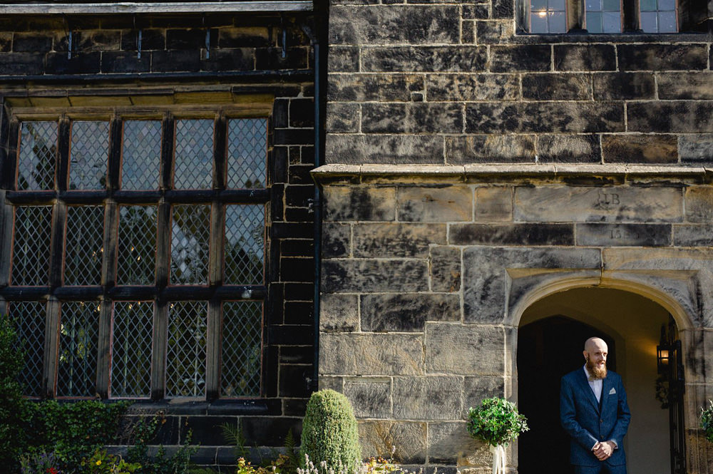 groom waiting for guests outside of oakwell hall