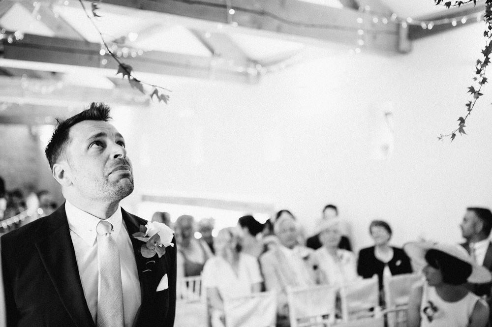 black and white photo of groom waiting for bride in wedding barn Wetherby
