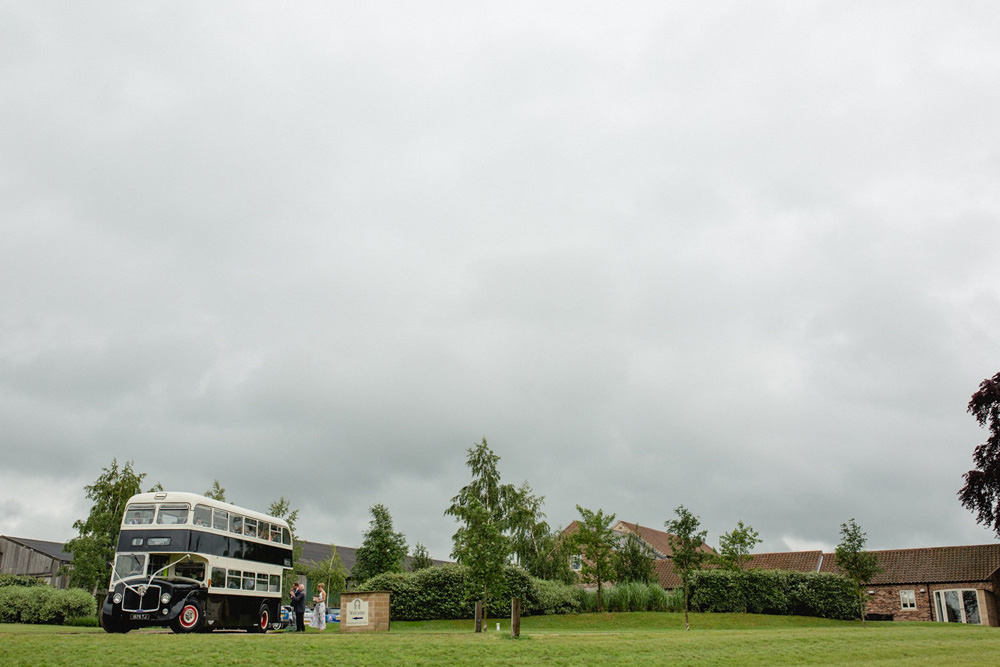 guests arriving on vintage bus at wedding barn