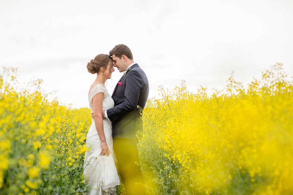 outdoor portrait of wedding couple in corn fields at priory cottages wedding barn