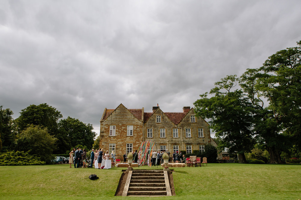 Outdoor wedding ceremony with Talton Lodge as background