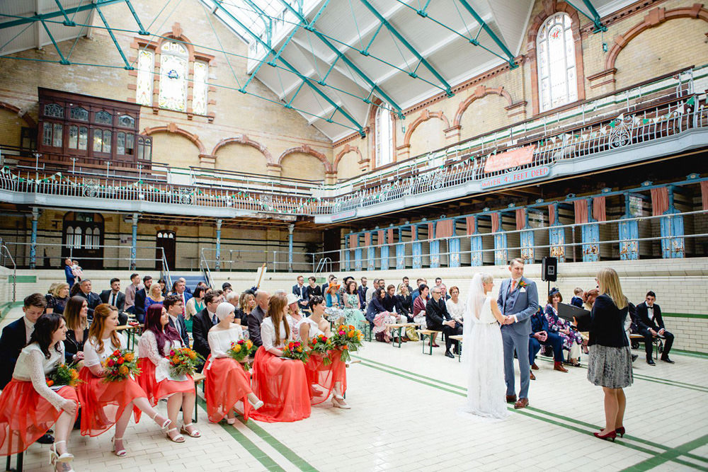 Ceremony in the main swimming pool at The Turkish Baths stained glass window at Victoria Baths Wedding Venue Manchester