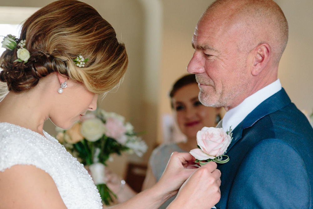 natural wedding photography moment between bride and dad as she puts his flowers on