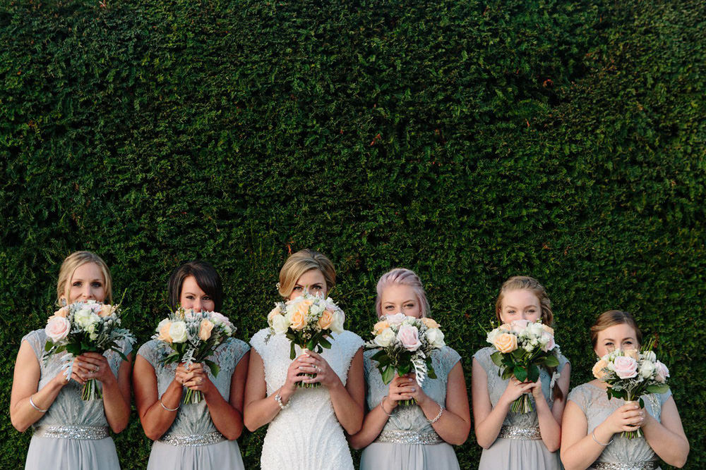 fun group photo of bridesmaids with flowers